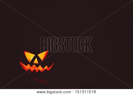 Glowing Pumpkin Symbolizing The Head Of Old Jack On Night Spooky Dark Background. Soft Focus. Shallo