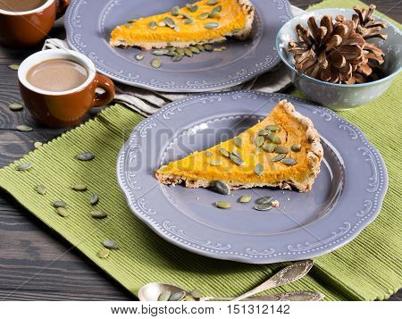 Slice of fall shortcrust pumpkin pie with pumpkin seeds on rustic wooden table with green napkin