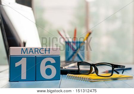 March 16th. Day 16 of month, calendar on business office background, workplace with laptop and glasses. Spring time, empty space for text.