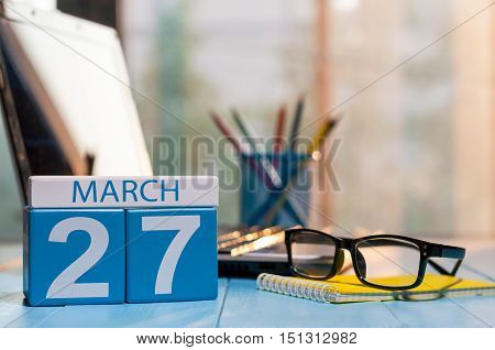 March 27th. Day 27 of month, calendar on business office background, workplace with laptop and glasses. Spring time, empty space for text.