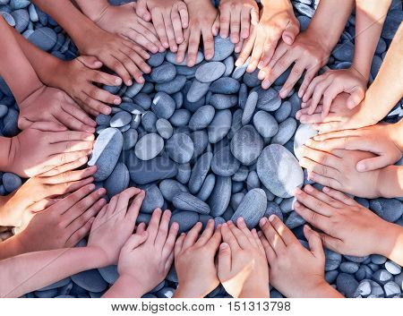 A lot of children's hands in a circle on the stones.