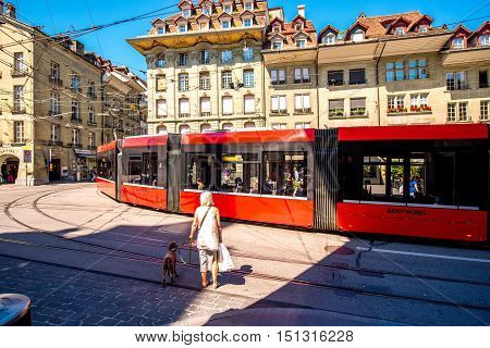 Bern, Switzerland - June 24, 2016: Street view with red tram, elder woman and dog cross the street in the old town of Bern city. Life in Bern city.