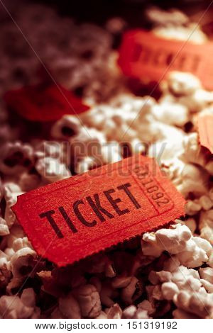 Close Up of Red Numbered Tickets on Top of Freshly Popped Movie Popcorn. Theatre and Festival Events