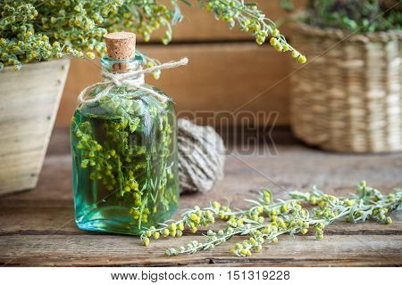 Bottle Of Absent Or Tincture Of Tarragon, Absinthe Healing Herbs On Old Wooden Table. Herbal Medicin