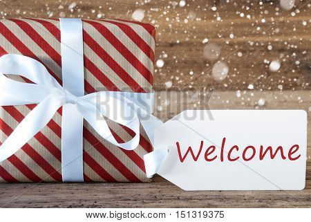 Christmas Gift Or Present On Wooden Background With Snowflakes. Card For Seasons Greetings. White Ribbon With Bow. English Text Welcome