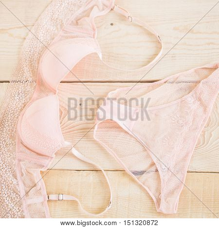 female erotic fashionable lace bra and panties or lingerie beige pink or peach color on wood or wooden background