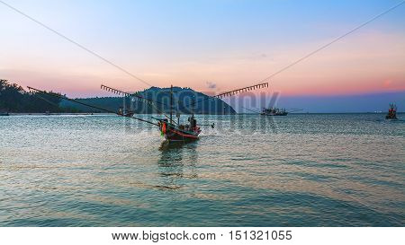 Beautiful sunset on the coast at the backdrop of green mountains. Fishing pier wooden boat in the sea off the coast. (Thailand).