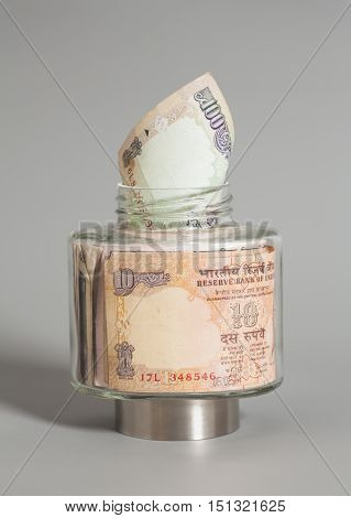 Money Indian Currency Rupee Notes in a glass jar on gray