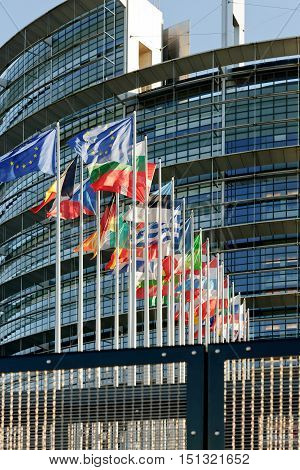 STRASBOURG FRANCE - JANUARY 28 2014: European Parliament facade with all EU European Union Country flags waving on a clear sky day as seen behind the security fence