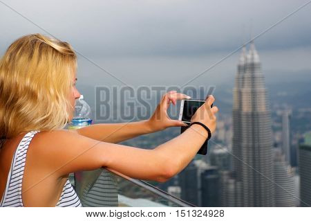KUALA LUMPUR MALAYSIA - January 17 2016: Travel and technology. a Young woman taking photo with smartphone from KL- Tower at evening.
