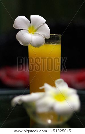 a freshly squeezed fresh orange juice close-up with a Magnolia blossoms on the glas