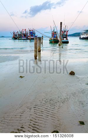 Fishing boats on the sandy shore at sunset Thailand.