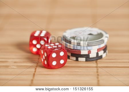 two red dices and gambling chips on wooden background