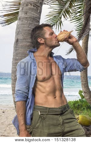 Muscular rugged Caucasian man with sexy torso wearing unbuttoned shirt drinks water from fresh coconut under palm tree on Caribbean island beach