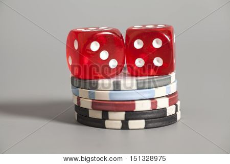 two red dices and gambling chips on gray background
