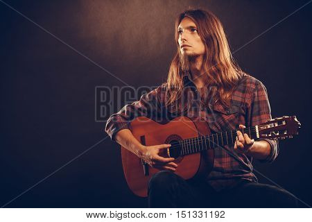 Young musican practicing with guitar. Male guitarist with instrument. Passion hobby playing acoustic concept.