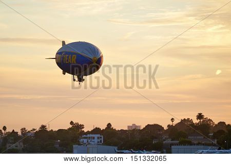 SANTA MONICA, CALIFORNIA USA - OCT 07, 2016: The Good Year blimp Zeppelin, Spirit of Goodyear with yellow stripe , flies over Santa Monica airport, USA. Rides aboard the Goodyear Blimp are by invitation only.
