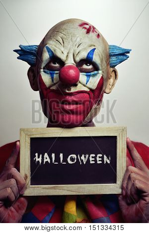 portrait of a scary evil clown with a chalkboard with the word Halloween written in it