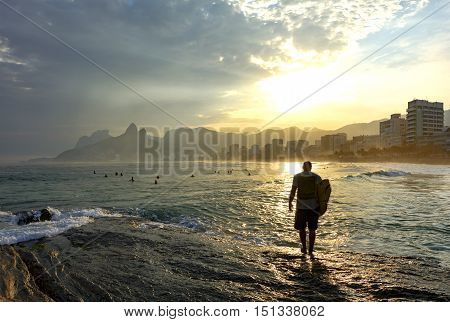 Surfer walking at sunset over the rocks in Arpoador beach at Ipanema in Rio de Janeiro
