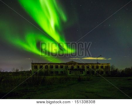Polar lights in the sky over the abandoned building