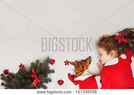 Little girl embracing puppy dog. Holiday concept Christmas New year background. High top view. Place of your text.