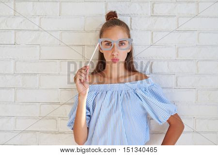Cool Caucasian girl wearing paper glasses puckering lips while posing at the camera