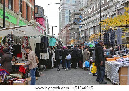 LONDON UNITED KINGDOM - NOVEMBER 24: Petticoat Lane Market in London on NOVEMBER 24 2013. Petticoat Lane Market With Clothing Stalls at Sunday in London United Kingdom.