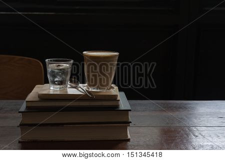 hot fresh coffee in see through glass water glass on big book on wooden tray and table silver spoon at coffee time / hot fresh coffee and book