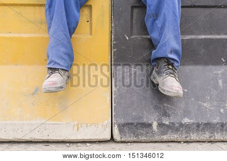 Construction Workman Boots on Concrete Barriers blocking at Building Site