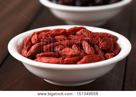 Dried gojis or wolfberries in small bowl photographed with natural light (Selective Focus Focus on the top berries)
