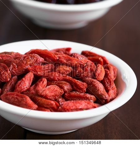 Dried gojis or wolfberries in small bowl photographed with natural light (Selective Focus Focus on the berries in the middle of the bowl)