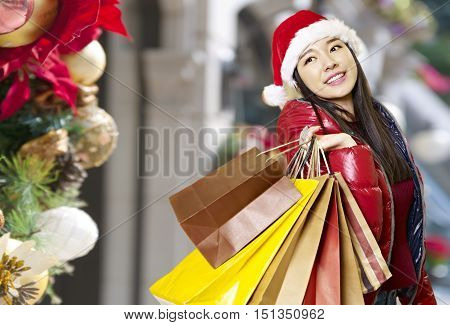 young asian woman carrying paper bags on shoulder during christmas shopping happy and smiling.