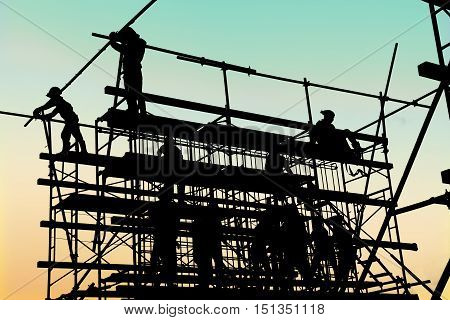 Silhouette of construction workers working on scaffolding at a high level by the standards set must include a safety belt for safety. Heavy industry And Safety at Work concept.
