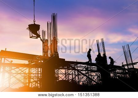 Silhouette construction industry engineer standing orders for construction team to work safely on high ground over blurred background sunset pastel for industry background. heavy industry concept.