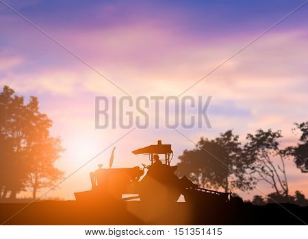 silhouette of heavy machinery working plowed soil in preparation for planting crops. Agriculture is the main industry and the stability of the world. concept food crop. concept to save the world.