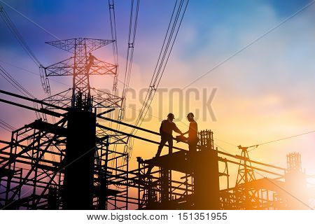 Silhouette engineer Good deal.two engineer business people shaking hands over blurred natural background sunset pastel. heavy industry and safety at work concept