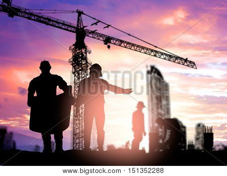 Silhouette engineer looking construction worker under tower cran in a building site over Blurred construction worker on construction site
