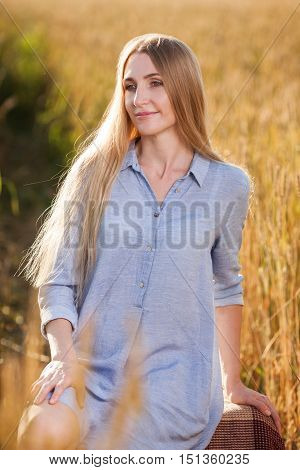 beautiful blonde middle age woman outdoors on wheat field