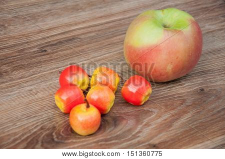 Six small apples and one big laying on brown wooden table.