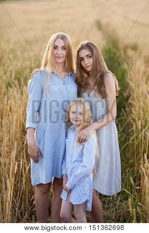 beautiful young mother and her daughters standing at the wheat field before sunset