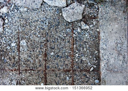 Grey concrete surface with visible reinforcement and crushed stones.