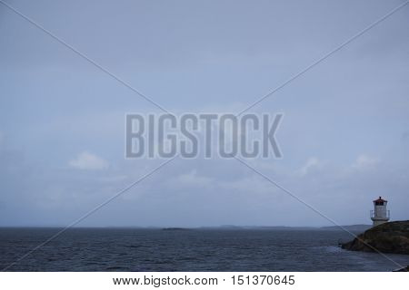 a small lighthouse in a vaste seascape
