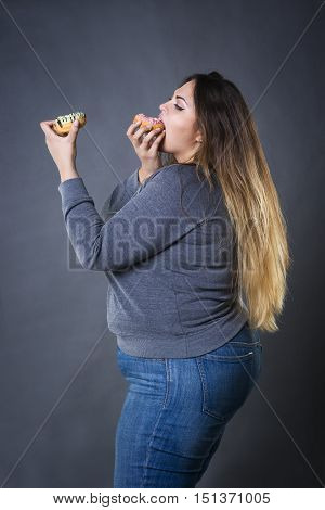 Beautiful young caucasian plus size model posing with donuts on a gray studio background fast food and unhealthy nutrition concept