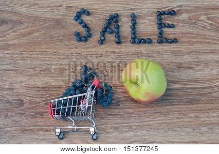Word sale made of blue grapes and bunch in small shopping cart and big green apple on brown wooden background