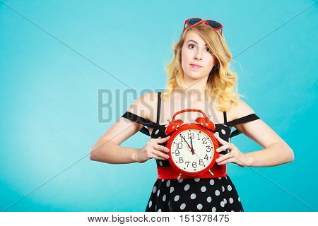Saving time concept. Blonde emotional girl worried expression wearing dotted dress with alarm clock on blue.