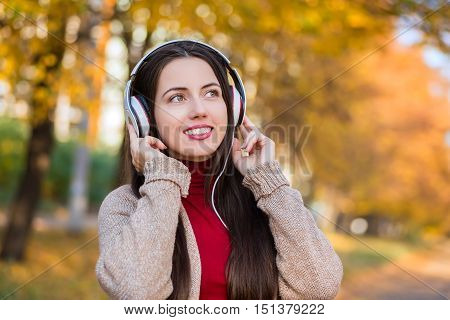 Young caucasian brunette woman with headphones outdoors on autumn day. Girl listening music in headphones in autumn park. Portrait of woman at outdoor with headphones. Autumn portrait of girl