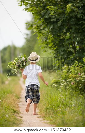 Back view on cute bare feet kid boy in straw hat running on a countryside road and holding bunch of wild flowers. Child running in the park. Outdoors. Happy summer and lifestyle concept. Childhood.