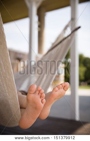 Foot of a child lying in the hammock and relaxing on a sunny day. Bare feet. Lifestyle concept.