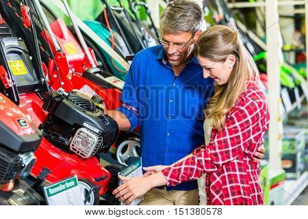 Hobby gardener couple, woman and man, in garden center of hardware store looking for lawnmower