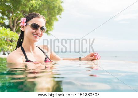 Woman in summer vacation relaxing swimming in pool with the ocean in the background